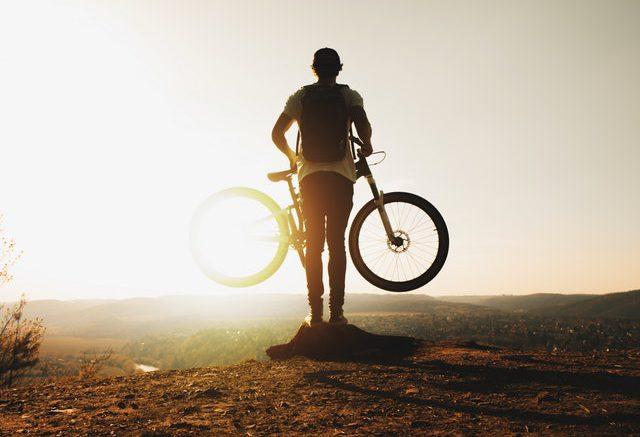 står med cykel i solen